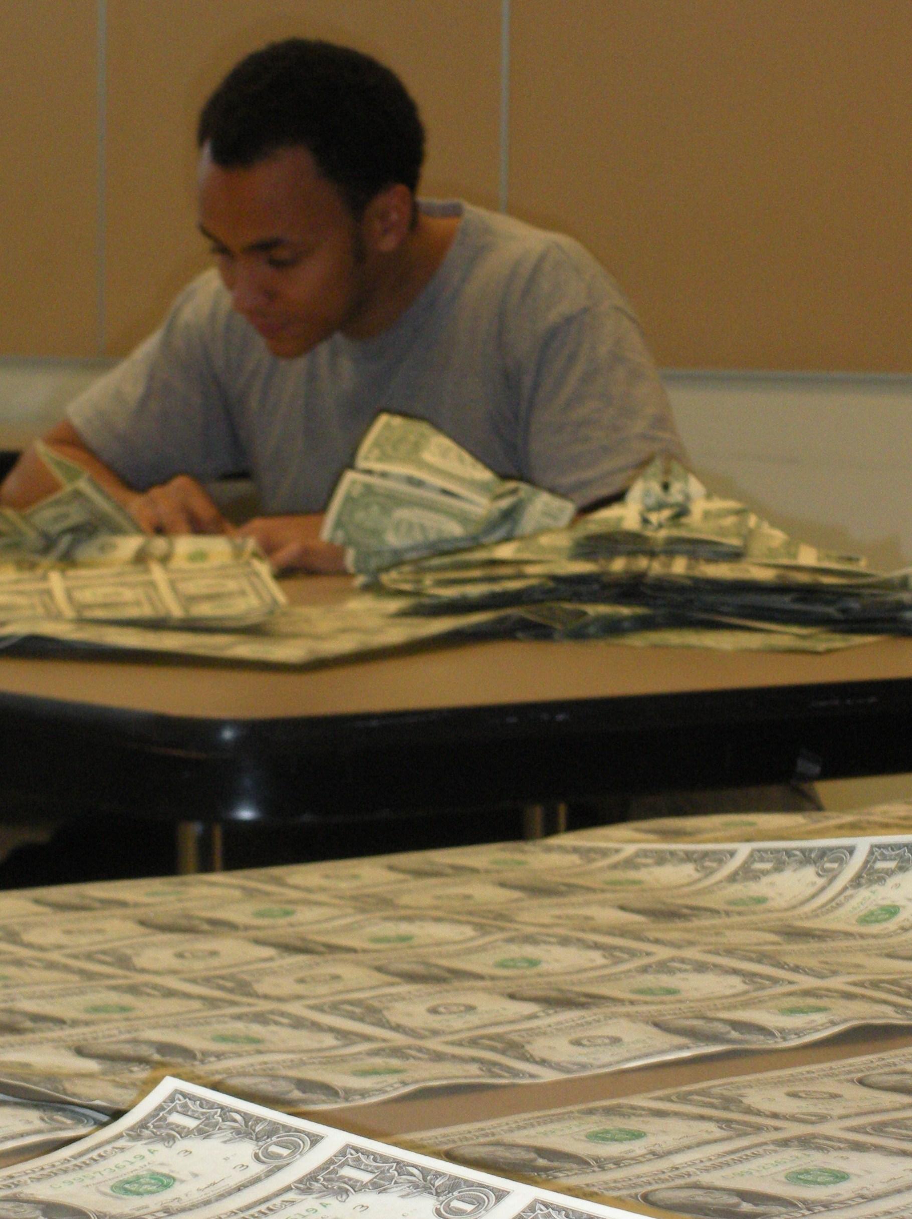 Sipho Mabona folding sheets of US dollar bills at JANM, March 2010