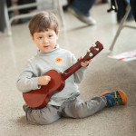 A young JANM guest strums along to the solo ukulele performances. Photo by M Palma.