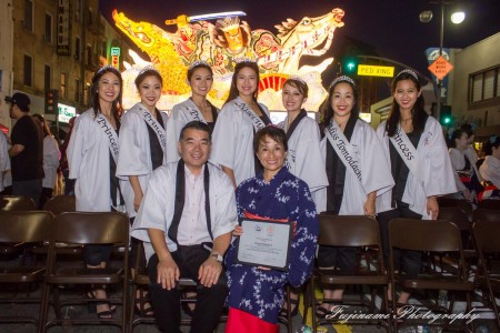The 2015 Nisei Week Court, with 2015 Nisei Week Foundation President Terry Hara and a community member, poses in front of the 2015 Nebuta float, designed especially for this year's parade by master Nebuta float artist Hiroo Takenami. Photo by John Fujinami.